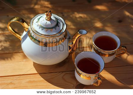 beautiful tea set, porcelain teapot, with beautiful pattern, gilt, and two cups with black tea, on wooden table, summer get-togethers on Fazenda poster