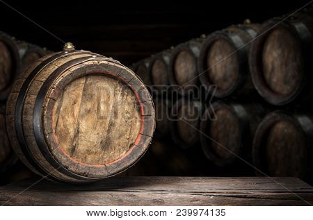 Wine barrel on the old wooden table. Wine cellar at the background.