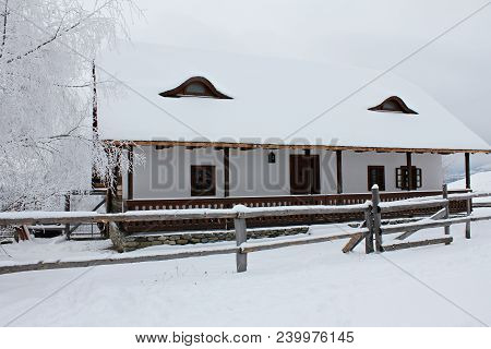 Winter Scene In The Mountains. Snow And Mountains And Cloudy Sky. Wood Cabin Is An Idyllic Place For