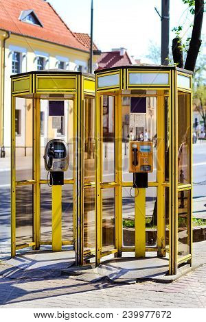 Yellow Glass Telephone Booths With Payphones Are Located On A Pedestrian Street. Obsolete Means Of T