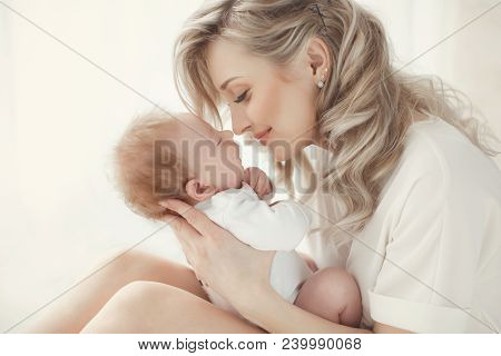 Young Mother Holding Her Newborn Child. Woman And New Born Boy Relax In A White Bedroom. A Young Mot