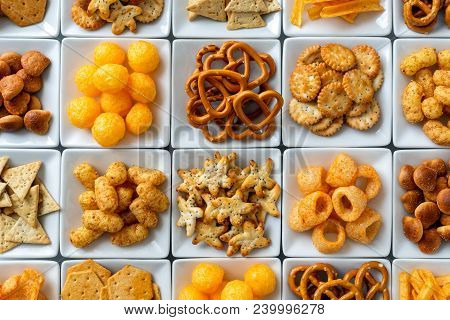 Background Of Many Types Of Savory Snacks In White Square Dishes From Above.