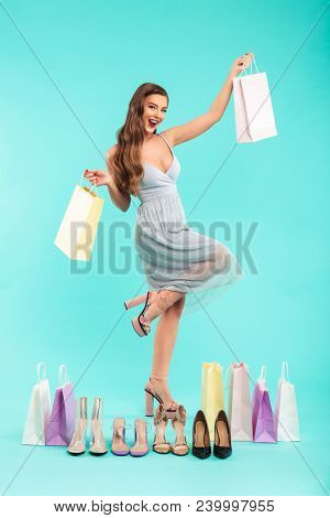 Full length photo of happy shopper woman 20s in dress smiling and holding shopping bags with shoes isolated over blue background