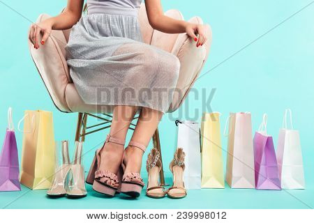 Cropped image of young shopper woman 20s sitting on armchair with lots of sandals and shopping packages isolated over blue background