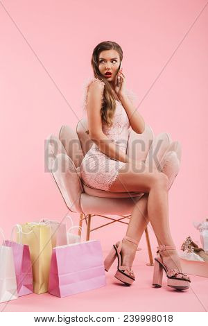 Full length photo of shopper woman in dress speaking on smartphone while sitting in armchair with shopping bags and shoes isolated over pink background