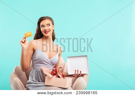 Shopping woman 20s in dress holding present box with shoes and credit card while sitting on armchair isolated over blue background poster