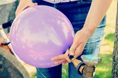 woman filling violet balloon with helium gas poster