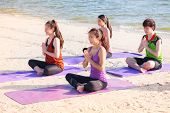 Yoga class at sea beach in sunny day ,Group of people doing namaste pose with clam relax emotion,Meditation pose,Wellness and Healthy balance lifestyle.. poster