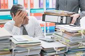 Stressed businessman working at office desk and overloaded with work, the desktop is covered with paperwork, his secretary is bringing more files poster