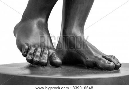 Foot. Fragment of an antique marble statue. Cracked ground in the background. Plaster limb, foot male with fingers, body part. Foots of ancient granite statue of man isolaated on white background