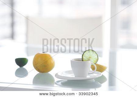 Tasse Tee mit tropischen Früchten auf einer Glasoberfläche