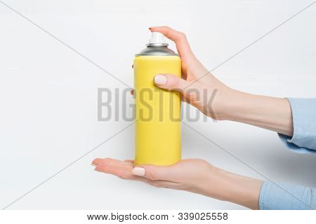 Yellow Spray Can For Spraying In A Female Hands. No Inscriptions. White Background