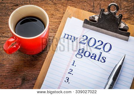 my 2020 goals list on clipboard and coffee against grunge wood desk, New Year resolutions concept
