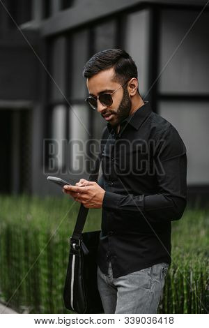 Stylish Gen Z Indian Arabic Guy Booking A Ride On His Taxi E-hailing App Using His Smartphone