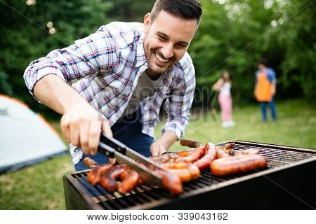 Man Cooking Meat On Barbecue Grill At Outdoor Summer Party