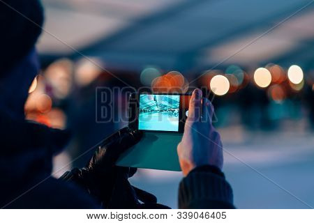 Male Hands Holding A Mobile Phone On Photo Camera Mode - Man Taking Picture Of A Ice Skating Rink By