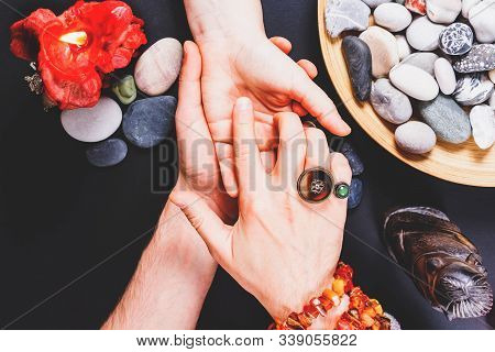 Fortune Teller Man Divines The Hand Of Young Woman Around Candles, Stones And Other Magical Parapher