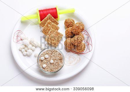 Til Gul Or Sweet Sesame Laddu In Glass Bowl With Fikri For Indian Festival Makar Sankranti Over Whit