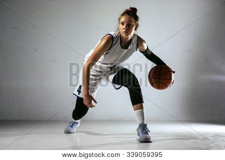Young Caucasian Female Basketball Player Of Team In Action, Motion In Run Isolated On White Wall Bac