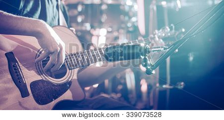 The Studio Microphone Records An Acoustic Guitar Close-up. Beautiful Blurred Background Of Colored L