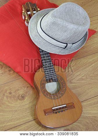 A Samba Player (sambista) Hat And A Cavaquinho, A Brazilian String Musical Instrument, On A Red Pill