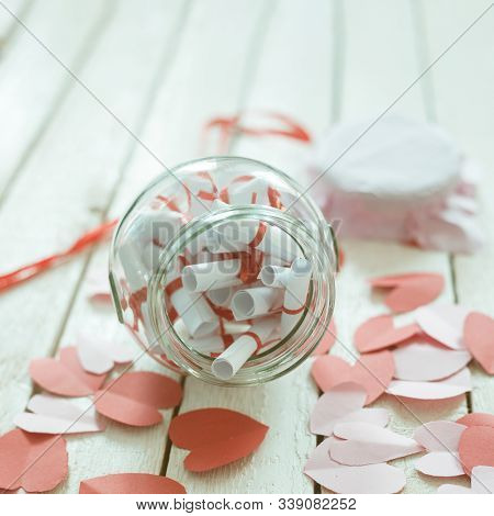 Valentine's Day Concept. Opened Date Jar With Desires And Paper Hearts On Wood