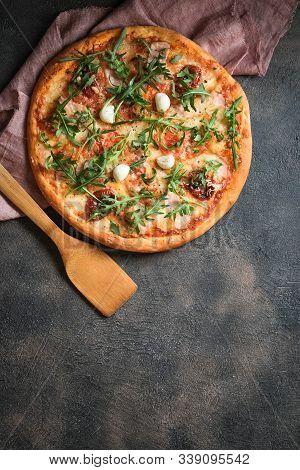 Traditional Italian Pizza With Ham, Mushrooms, Arugula, Mozzarella, Basil And Tomatoes On A Dark Bac