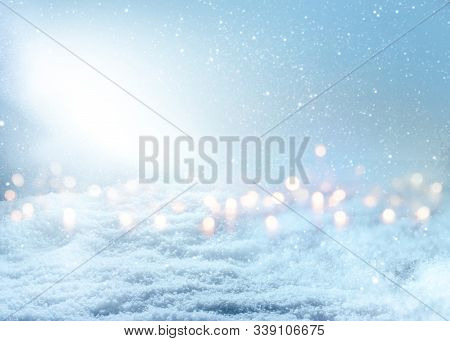 Blurred Blue Snowy Landscape With Bright Magical Light Beam And Bokeh. Background For A Wintery Chri