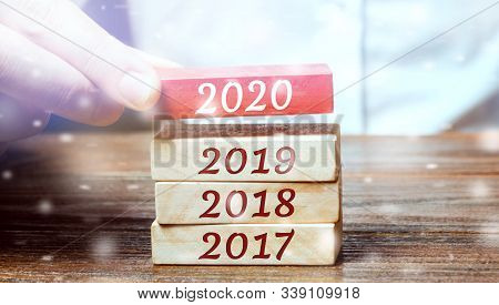 Businessman Builds Wooden Blocks 2020. The Concept Of The Beginning Of The New Year. New Goals. Next