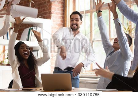 Excited Team Celebrating Successful Project Accomplishment Throwing Papers Up
