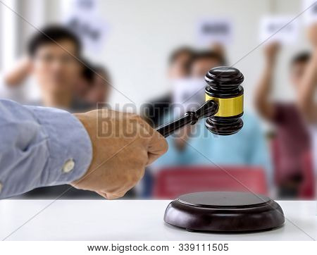 The Person Carrying The Auction Holds A Wooden Hammer In His Hand To Make A Bid To Sell The Product.