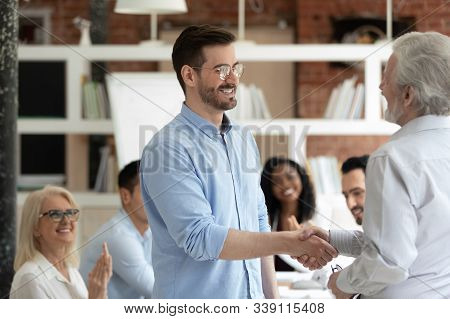 Aged Boss Welcoming New Employee With Handshake Symbol Of Respect