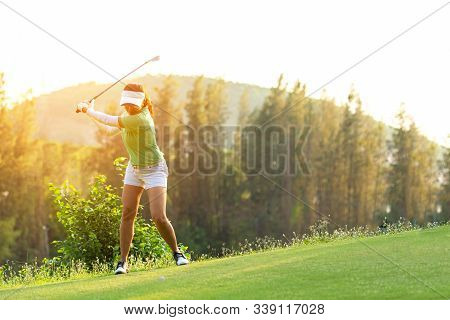 Asian Sporty Woman Golfer Player Doing Golf Swing Tee Off On The Green, People Presumably Does Exerc