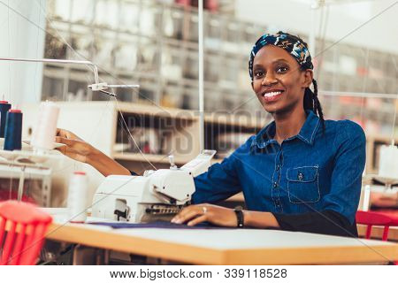 Young African Textile Worker Sewing On Production Line. Dressmaker Woman Working With Sewing Machine