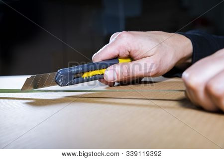Man Using An Utility Knife To Open A Cardboard Box. Male Hand Holding A Tool. Opening Packages. Unbo