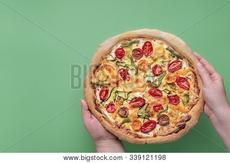 Pizza Primavera Held In Hands Over A Green Background. Spring Vegetarian Meal. Italian Pizza. Tradit