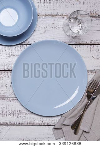 Blue Plates, Napkin And Cutlery On An Old White Wooden Background. View From Above.