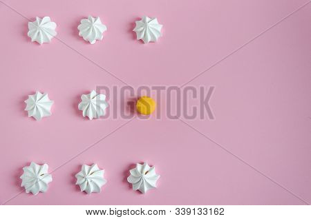 Meringue. White Air Meringues Lie In A Row On A Pink Background. The Rhythmic Pattern And One Yellow
