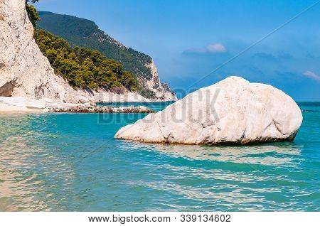 Massive White Boulder As A Sea Stack Lying In Water Of Adriatic Sea With Beautiful Coastline Of Numa