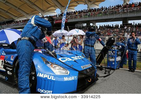 SEPANG - JUNE 10: Mechanics from the IMPUL team work on the Nissan GTR car on race day at the 2012 Autobacs SUPER GT Series Round 3 on June 10, 2012 at the Sepang International Circuit, Malaysia.