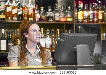 Portrait Of Woman Bartender Registrating New Order By Cash Register. A Restaurant Worker Registratin