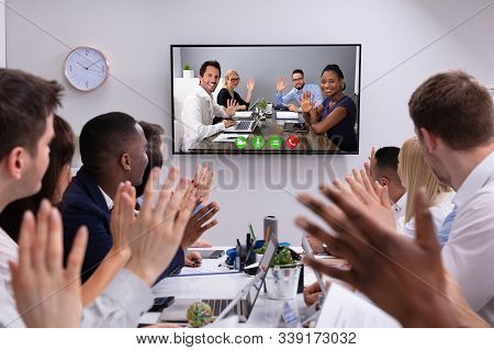 Group Of Business People Waving At Each Other Through Video Conference Meeting At Office