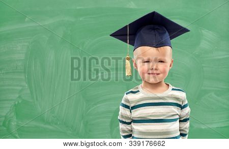 elementary school, preschool education and childhood concept - portrait of smiling little boy in mortar board over green chalk board background
