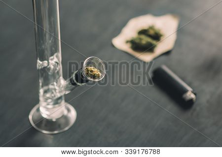 Sativa And Indica Bong And Marijuana, Cannabis Thc Flower Close Up On A Black Background. Lifestyle