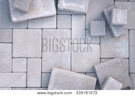 Laying gray concrete paving stones on house courtyard. Pavement background
