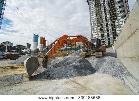 Large Orange Excavator Working On A Gravel On Construction Site. Details Of Industrial Excavator. Bi