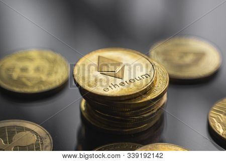Stack Of Golden Ethereum Bitcoin Coin With A Lot Of Bitcoins Coins On A Table. Virtual Cryptocurrenc