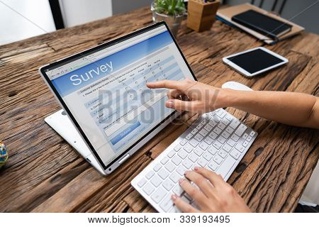 Cropped Image Of Businesswoman Giving Online Survey On Laptop At Office Desk
