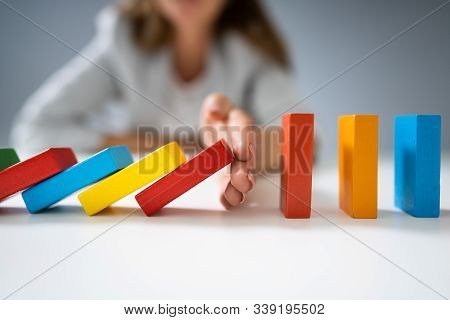High Angle View Of A Businessperson Stopping Colorful Dominoes From Falling On Desk
