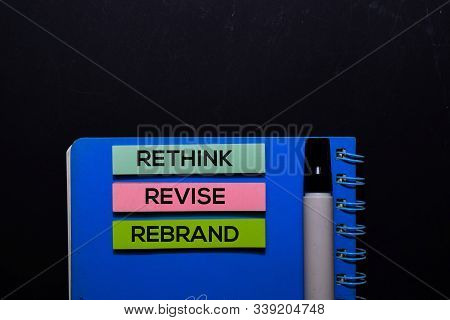 Rethink Revise Rebrand Write On Sticky Notes. Top View Isolated On Black Background.